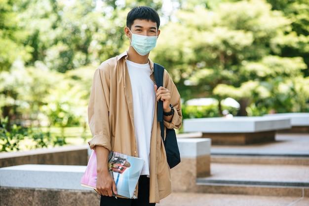 Os homens usam máscaras, carregam livros e carregam uma mochila nas escadas.