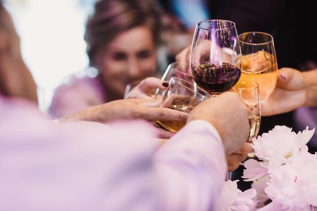Os hóspedes levantam copos com bebida diferente
