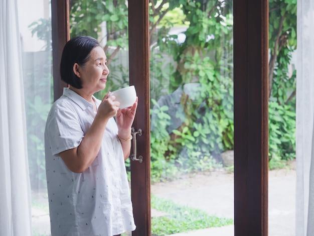 Os idosos pensando algo com beber café