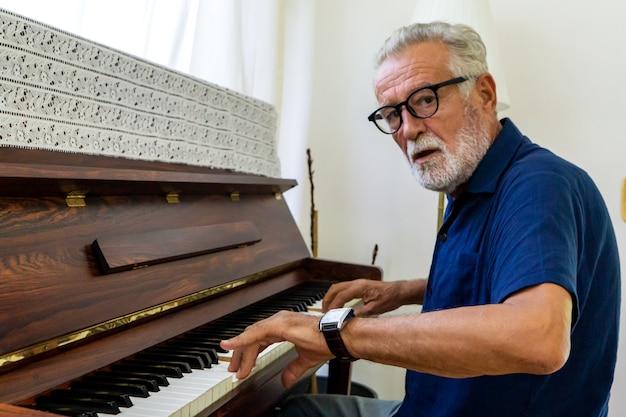 Os idosos praticam tocar piano em casa sozinhas