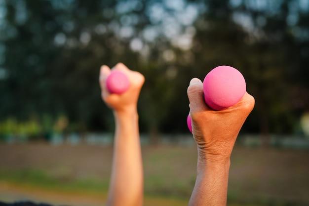 Os idosos seguram um haltere rosa para exercitar a saúde no jardim.