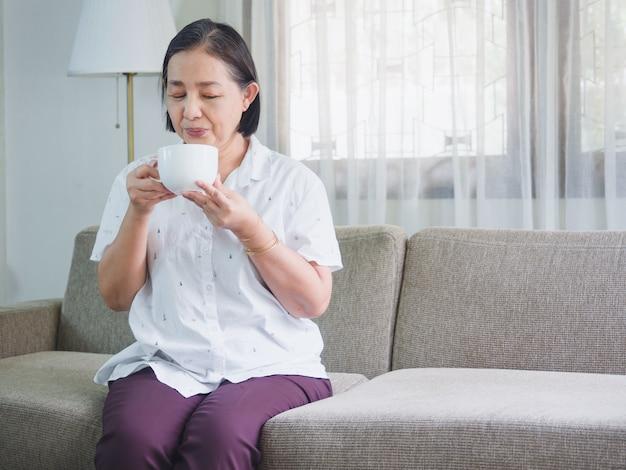 Os idosos sentam felizes em tomar café