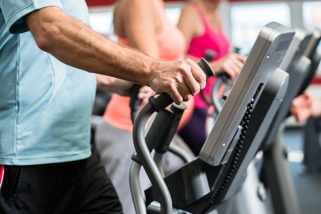 Os idosos treinam em cross trainer com personal trainer no ginásio