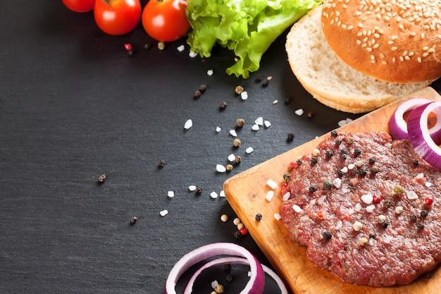 Os ingredientes crus para o hambúrguer caseiro em fundo de ardósia preta com espaço de cópia.