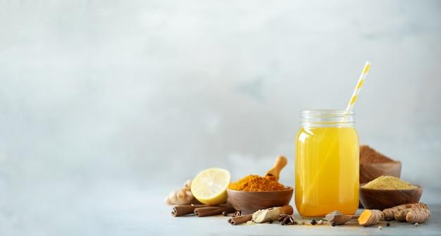 Os ingredientes para a cúrcuma alaranjada bebem no fundo concreto cinzento. água de limão com gengibre, curcuma, pimenta preta.