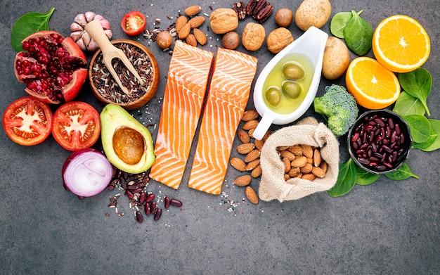 Os ingredientes para a seleção saudável dos alimentos setup no espaço concreto escuro da cópia do fundo.