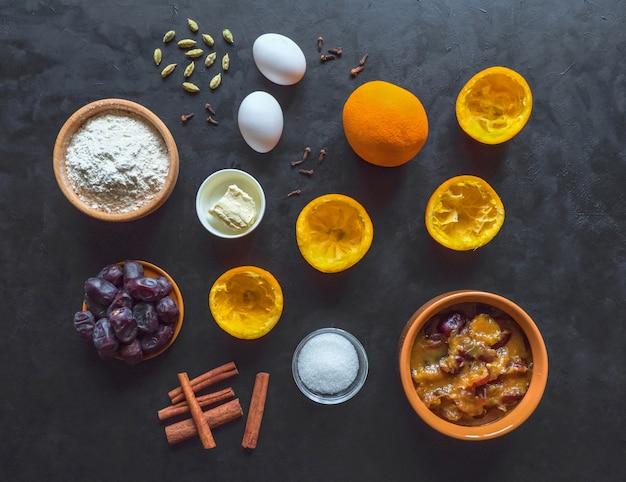 Os ingredientes para o bolo de data são dispostos em uma mesa preta. cozinha do ramadã.