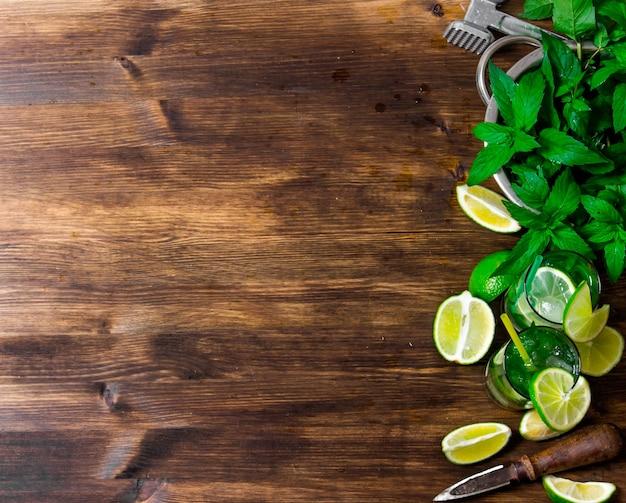 Os ingredientes para o coquetel - limão, rum, folhas de hortelã, cubos de gelo na mesa de madeira