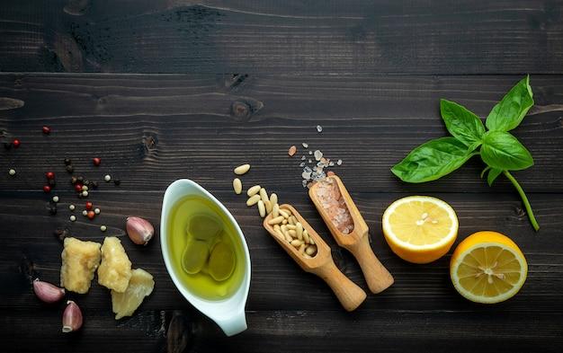 Os ingredientes para o molho pesto verde sobre fundo escuro de madeira.