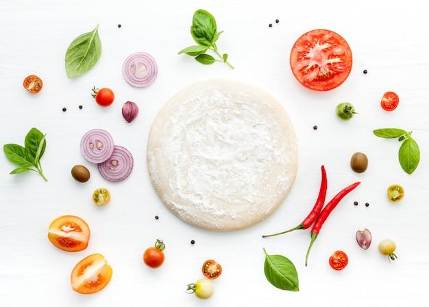 Os ingredientes para pizza caseira em fundo branco de madeira.