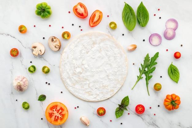 Os ingredientes para pizza caseira montados em fundo de mármore branco com espaço de cópia e vista superior.