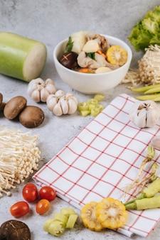 Os ingredientes usados para fazer a sopa incluem milho, cogumelos shiitake, tomates, cogumelos agulhas, pimenta e alho.