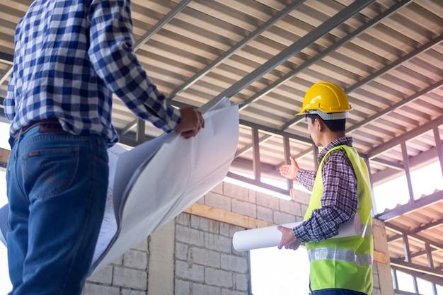 Os inspectores verificam a integridade da construção da casa. discuta métodos e resolva problemas de estrutura de construção com empreiteiros ou engenheiros.