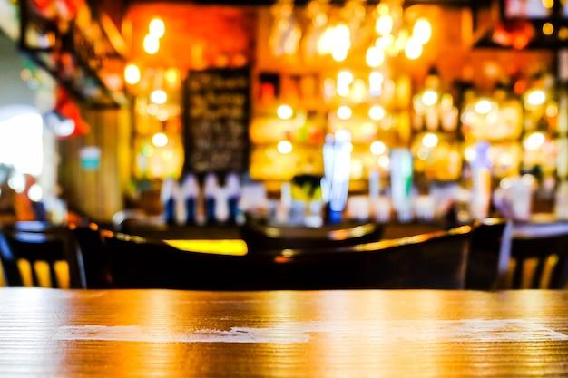 Os interiores opõem a barra com luz alaranjada e primeiro plano de madeira - borre o conceito do fundo.