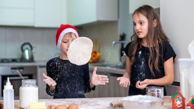 Os irmãos estão cozinhando na cozinha, o menino com chapéu de natal está vomitando a massa. ideia de criança feliz