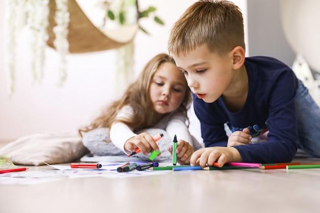 Os irmãos estão segurando lápis brilhantes e desenhando no chão
