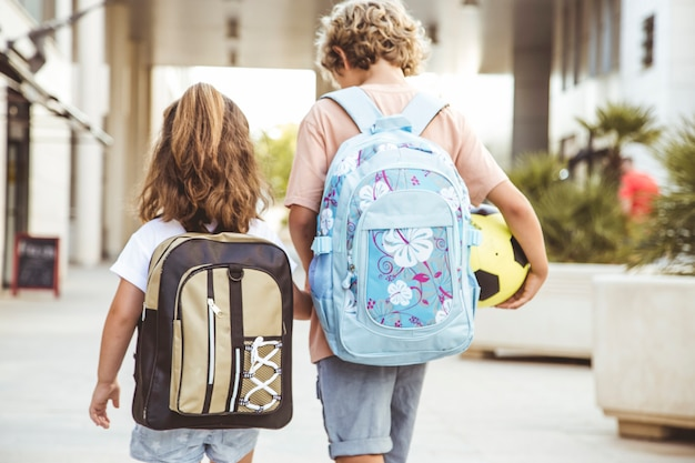 Os irmãos vão à escola com suas mochilas e uma bola de futebol.
