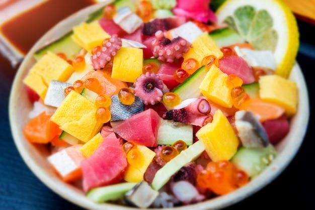 Os japoneses misturam salada de sashimi com arroz.