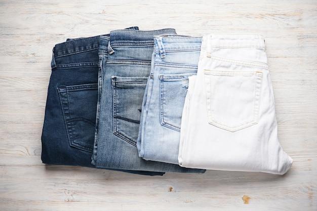 Os jeans são empilhados sobre uma mesa de madeira, plana.