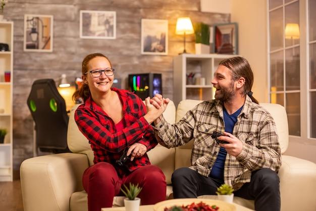 Os jogadores acoplam-se a jogar videogame na tv com controladores sem fio nas mãos.