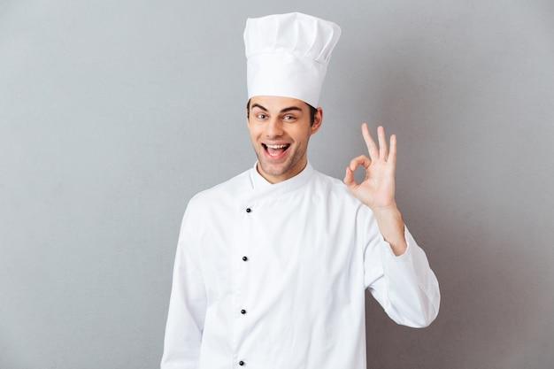 Os jovens alegres cozinham no uniforme que mostra o gesto aprovado.