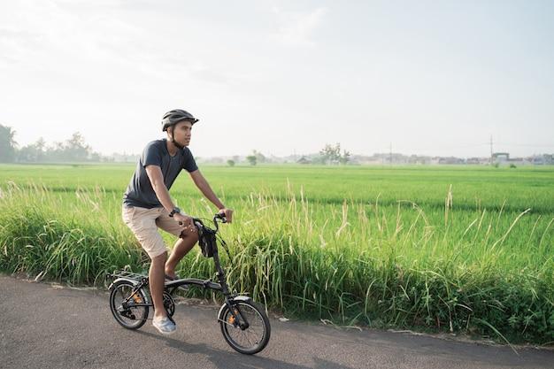 Os jovens asiáticos usam capacetes para andar de bicicleta dobrável nos campos de arroz