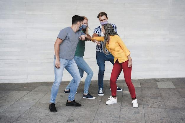 Os jovens batem os cotovelos em vez de cumprimentarem com um abraço - foco principal no rosto da garota africana