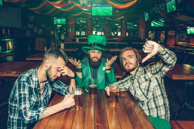 Os jovens chateados e infelizes sentam-se à mesa no pub. eles têm canecas de cerveja. homem de meia roupa de st. patrick.
