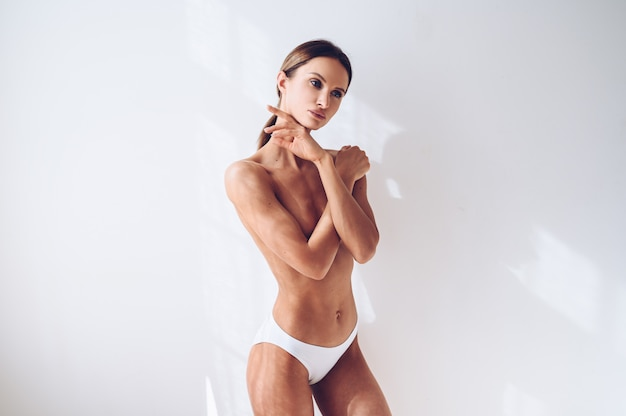 Os jovens couberam a mulher na roupa interior branca na parede branca isolada. mulher atraente magro muscular com barriga lisa. copie o espaço para texto. cuidados com o corpo, vida saudável e esportiva, depilação, conceito de ioga
