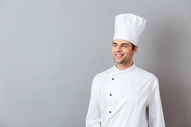 Os jovens cozinham em pé uniforme isolado