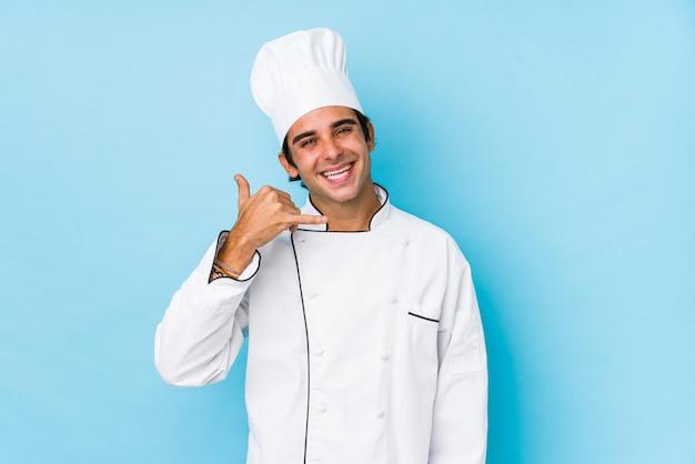 Os jovens cozinham o homem isolado mostrando um gesto de chamada de telefone móvel com dedos.
