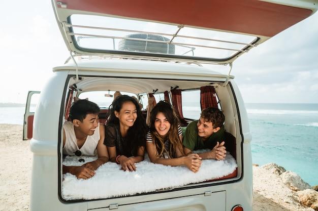 Os jovens desfrutam de férias estabelecer relaxar dentro de van vintage