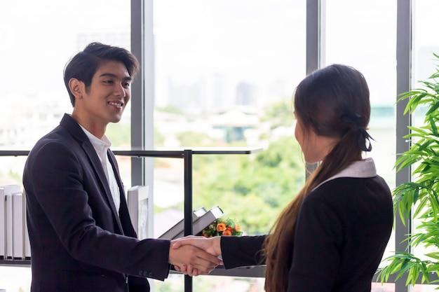 Os jovens empresários asiáticos juntam as mãos às mulheres de negócios no escritório.