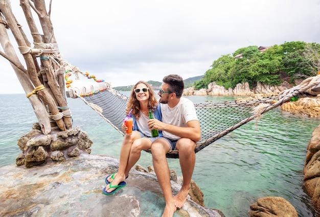 Os jovens engraçados felizes sorridentes bonitos novos um homem e uma mulher melhores amigas em uma rede nas férias bebem bebidas refrescantes