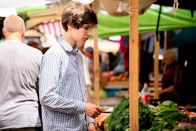 Os jovens escolhem vegetais frescos maduros no mercado ao ar livre e compram-nos