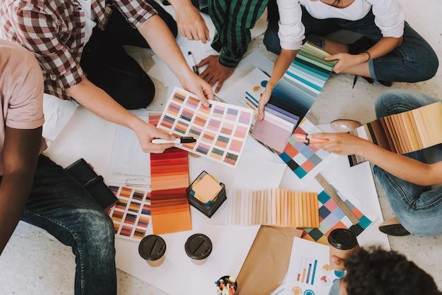 Os jovens estão trabalhando com paletas de cores.