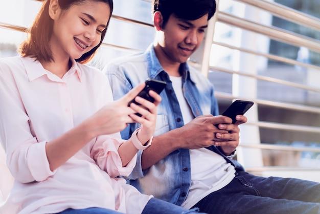 Os jovens estão usando smartphone e sorrindo enquanto está sentado no tempo livre. conceito de tecnologia