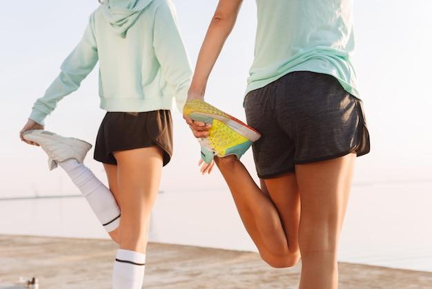 Os jovens fortes dois esportes mulheres amigos ao ar livre na praia fazem exercícios