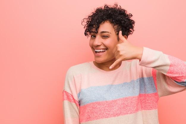 Os jovens misturaram a mulher afro-americano do adolescente que mostra um gesto de chamada de telefone móvel com os dedos.