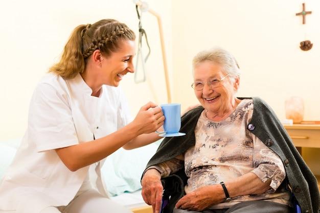 Os jovens nutrem e fêmea sênior no lar de idosos