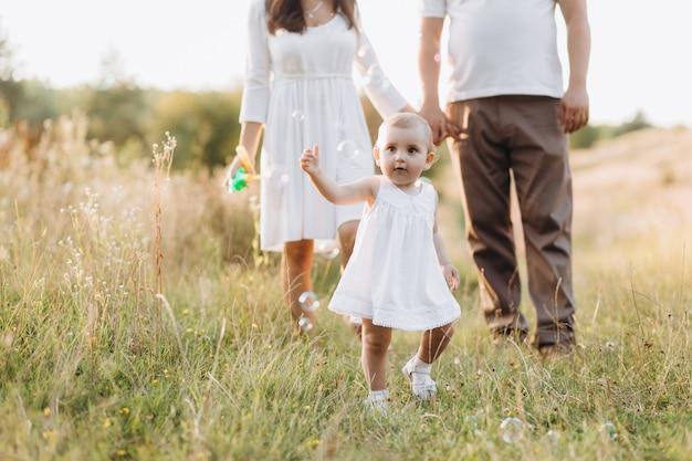 Os jovens pais andam com sua linda filhinha em jeans vestido em todo o campo