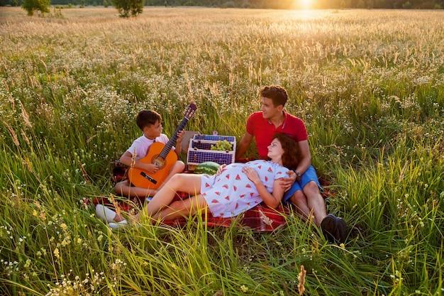 Os jovens pais e seu filho fazendo um piquenique no campo de trigo em um dia ensolarado. o filho está tocando violão para os pais. sessão de fotos da família grávida na natureza
