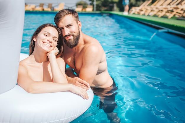 Os jovens positivos e positivos estão nadando na piscina. garota faz isso no colchão de ar. cara está nadando na água e inclinando-se para a garota. eles parecem felizes.