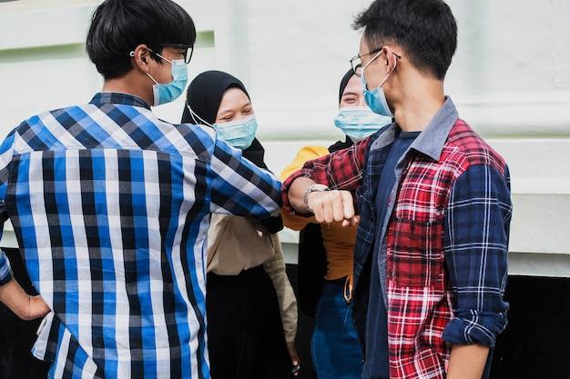 Os jovens se cumprimentam com o cotovelo ou normalidade de novo aperto de mão no vírus corona