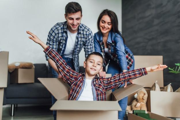 Os jovens se divertem enquanto se mudam para um novo apartamento. os pais empurram a caixa com o filho e brincam com ele