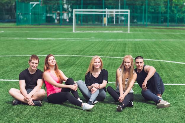Os jovens sentam na grama no campo de futebol.