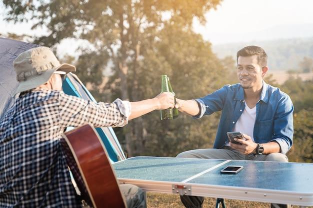 Os jovens vão acampar no verão no parque nacional com cerveja e uma pequena festa de violão. foto grátis