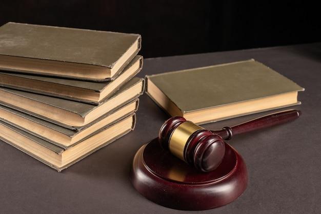 Os juízes martelam o documento legal com os livros jurídicos na mesa do advogado. conceito de decisão judicial jurisprudência, educação em direito.