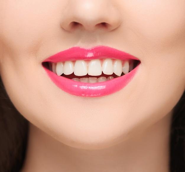 Os lábios vermelhos sensuais, boca aberta, dentes brancos.