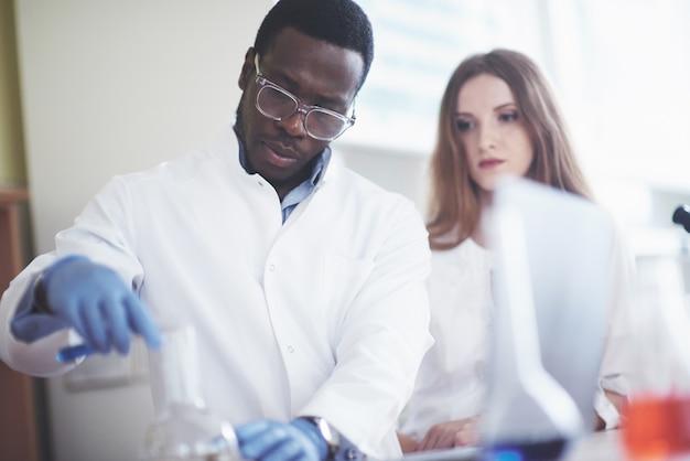 Os laboratórios de laboratório conduzem experimentos em um laboratório químico em frascos transparentes. fórmulas de saída.